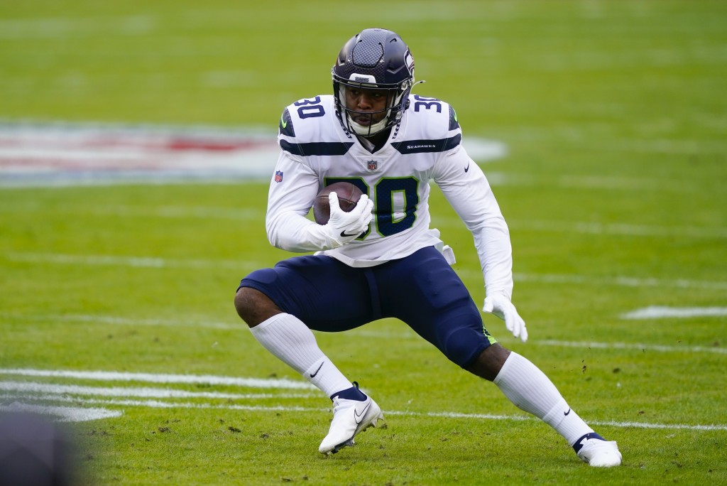 Seattle Seahawks running back Carlos Hyde (30) runs with the ball during the first half of an NFL football game against the Washington Football Team, ...