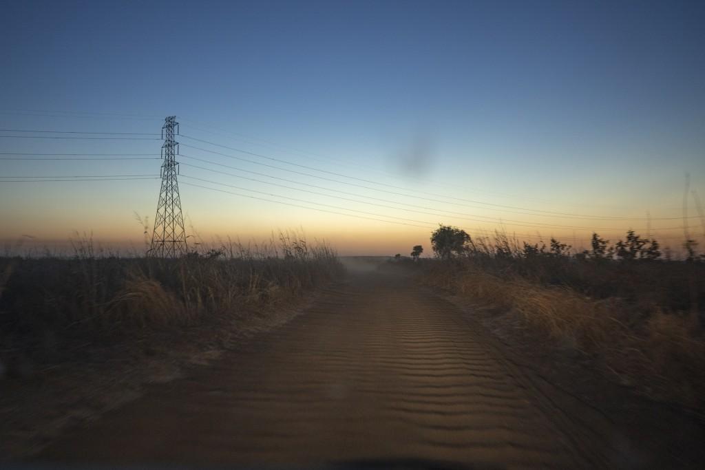 The sun sets nears the entrance of Umm Rakouba refugee camp in Qadarif, eastern Sudan, Sunday Dec. 13, 2020. (AP Photo/Nariman El-Mofty)