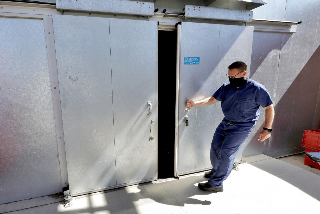 FILE - In this July 29, 2020, file photo, Pima County Medical Examiner Dr. Greg Hess opens the overflow body storage cooler at the medical examiner's ...
