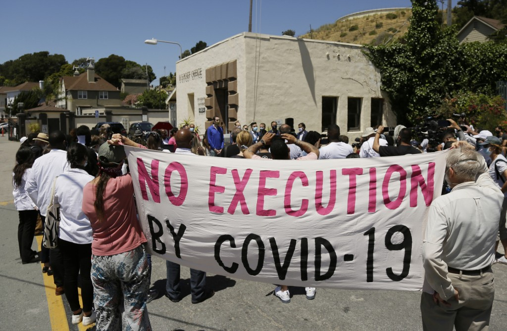 FILE - In this July 9, 2020, file photo, people hold up a banner while listening to a news conference outside San Quentin State Prison in San Quentin,...