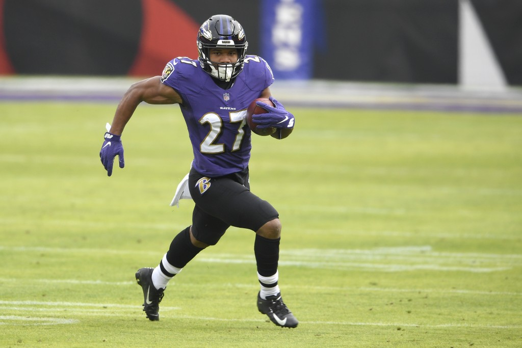 Baltimore Ravens running back J.K. Dobbins runs with the ball against the Jacksonville Jaguars during the first half of an NFL football game, Sunday, ...