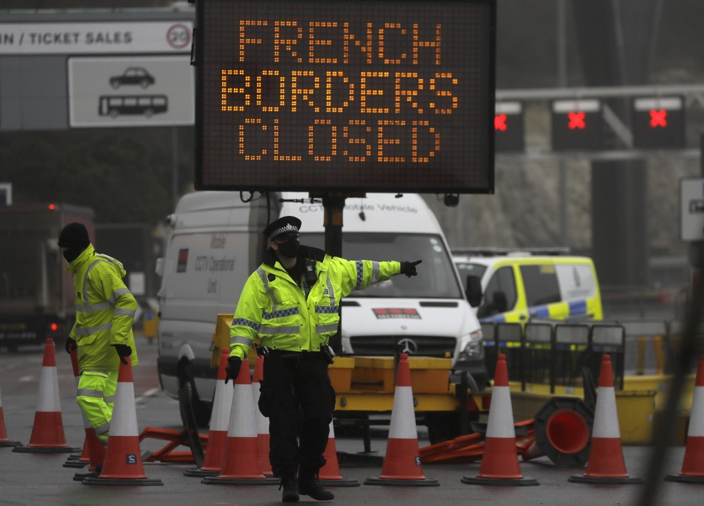 A police officer directs traffic at the entrance to the closed ferry terminal in Dover, England, Monday, Dec. 21, 2020, after the Port of Dover was cl...