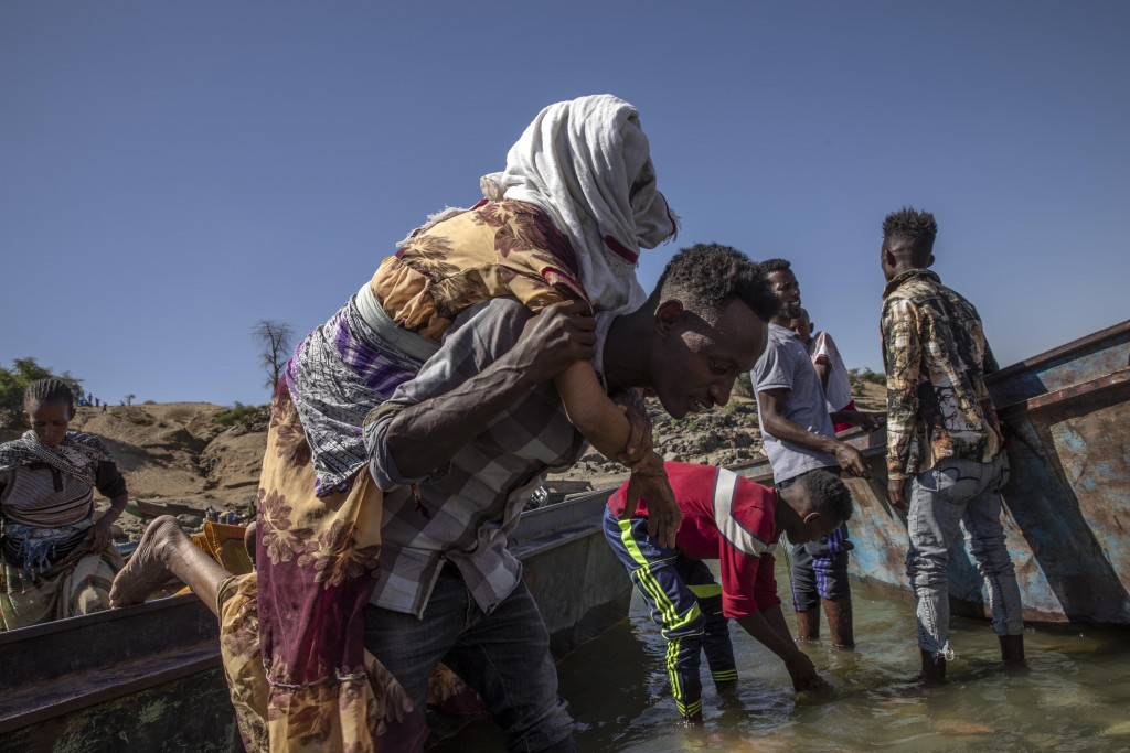 Tigrayan refugees who fled the conflict in the Ethiopia's Tigray arrive on the banks of the Tekeze River on the Sudan-Ethiopia border, in Hamdayet, ea...