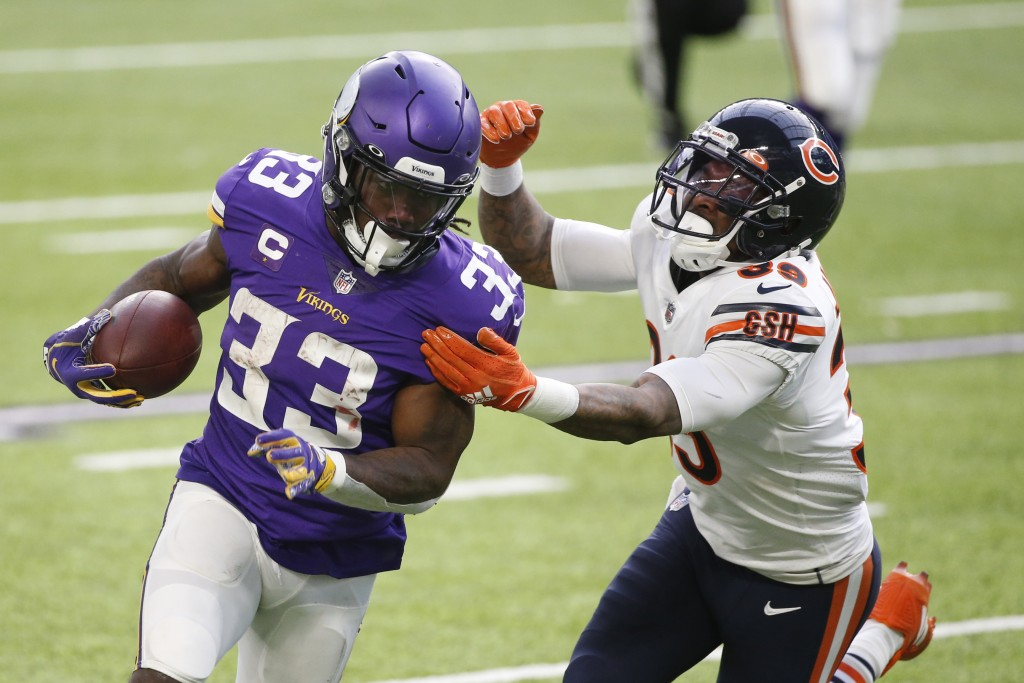 Minnesota Vikings running back Dalvin Cook (33) runs from Chicago Bears safety Eddie Jackson (39) during the first half of an NFL football game, Sunda...