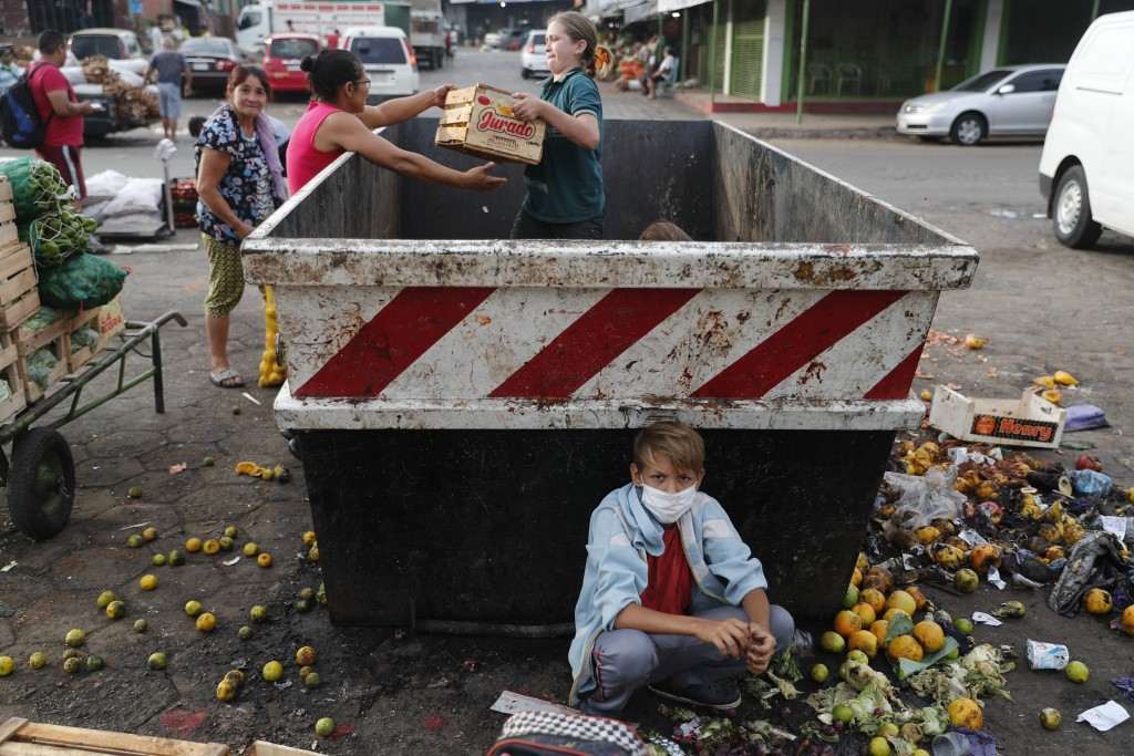 """Fabian Ramirez, 11, and members of his family scavenge a trash container for discarded vegetables at the """"Mercado de Abasto,"""" a market for vendors, du..."""