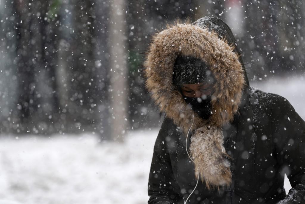 FILE - In this Dec. 17, 2020, file photo, a woman walks through a snowstorm in the Bronx borough of New York. (AP Photo/Mark Lennihan, File)