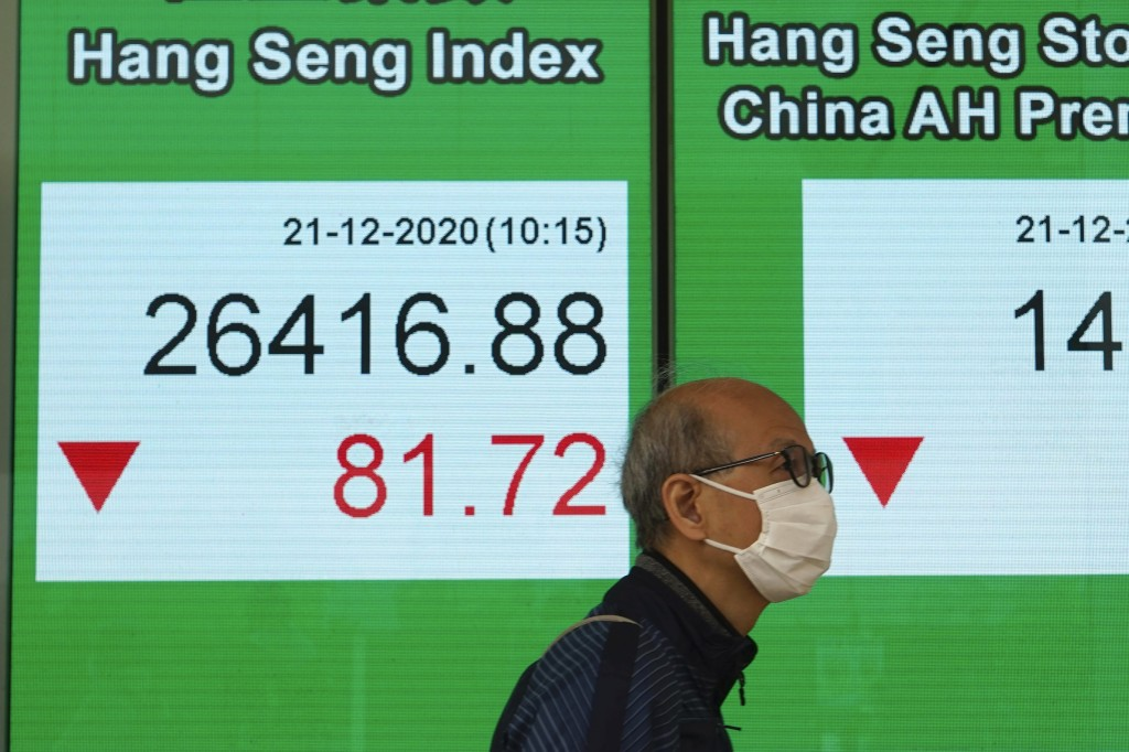 A man wearing a face mask walks past a bank's electronic board showing the Hong Kong share index in Hong Kong, Monday, Dec. 21, 2020. Shares have star...
