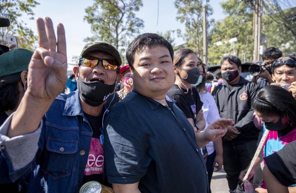 A supporter poses for a photo with pro-democracy protest leader Parit Chiwarak, center, outside Bang Khen Metropolitan Police Station, Bangkok, Thaila...
