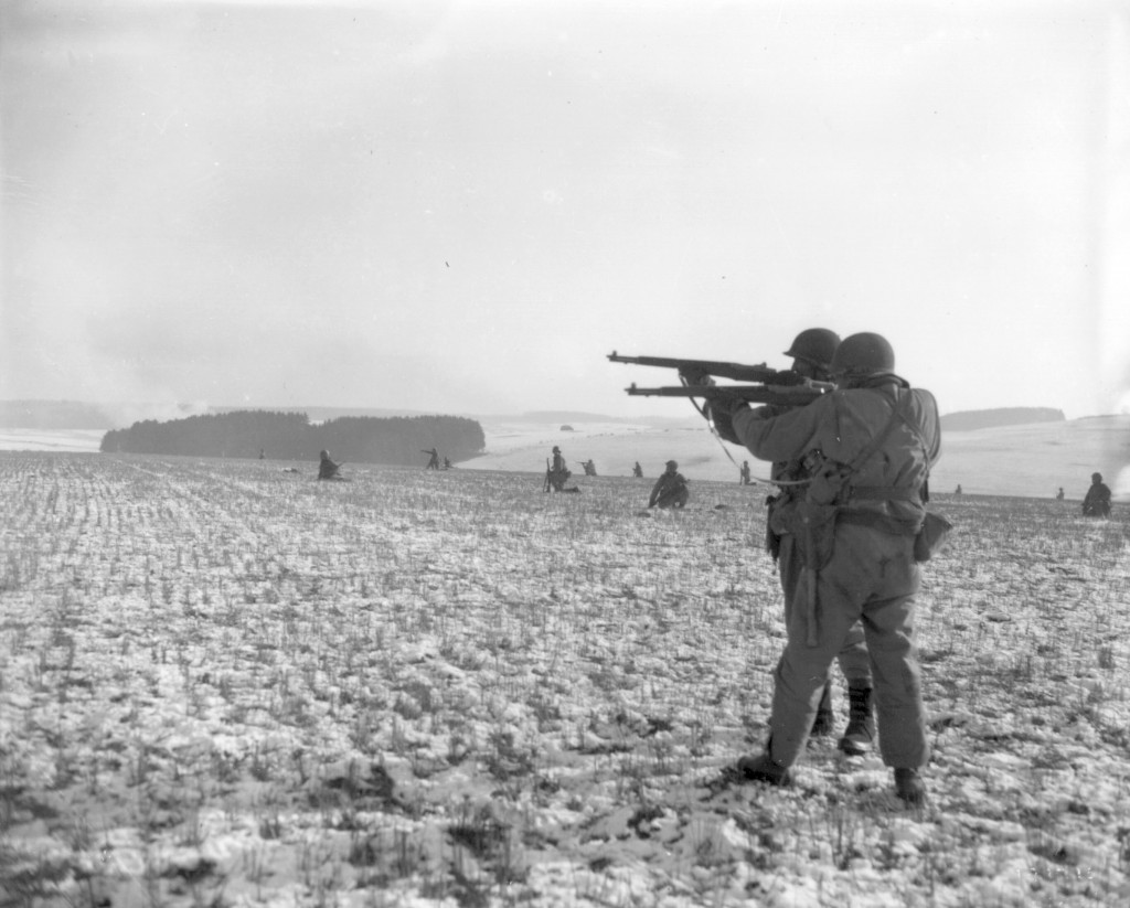 FILE - In this Dec. 27, 1944, file photo, American infantrymen of the 4th Armored Division fire at German troops, in an advance to relieve pressure on...