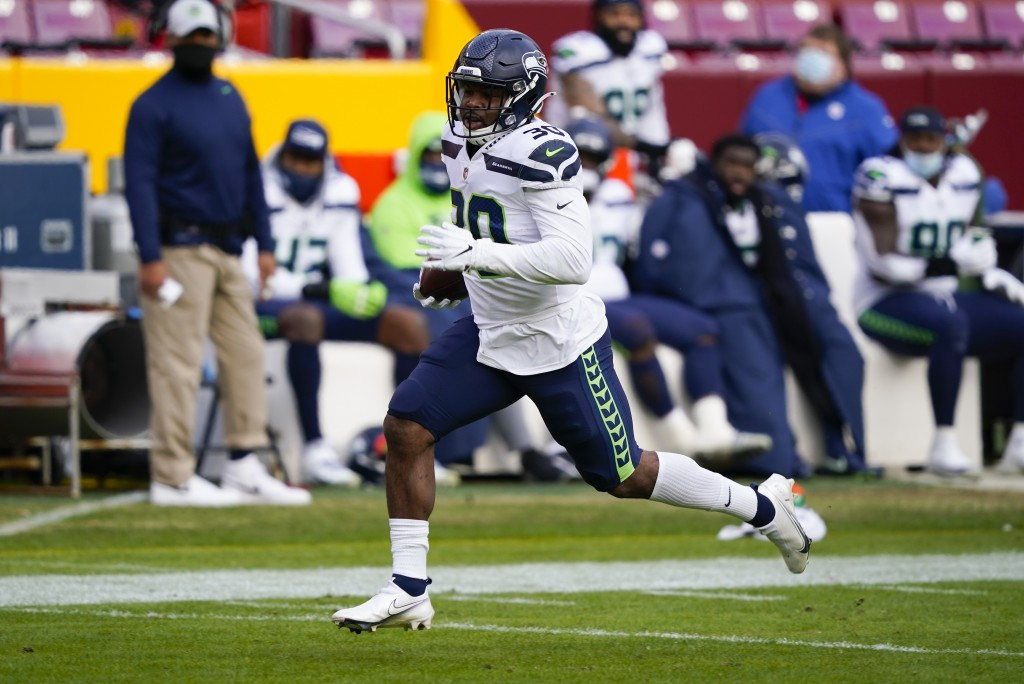 Seattle Seahawks running back Carlos Hyde (30) carries the ball during his 50-yard touchdown run against the Washington Football Team, Sunday, Dec. 20...