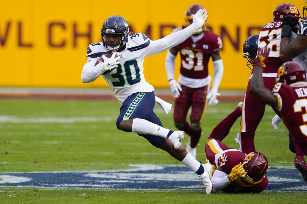 Seattle Seahawks running back Carlos Hyde (30) breaks away from Washington Football Team cornerback Ronald Darby (23) to begin his 50-yard touchdown r...