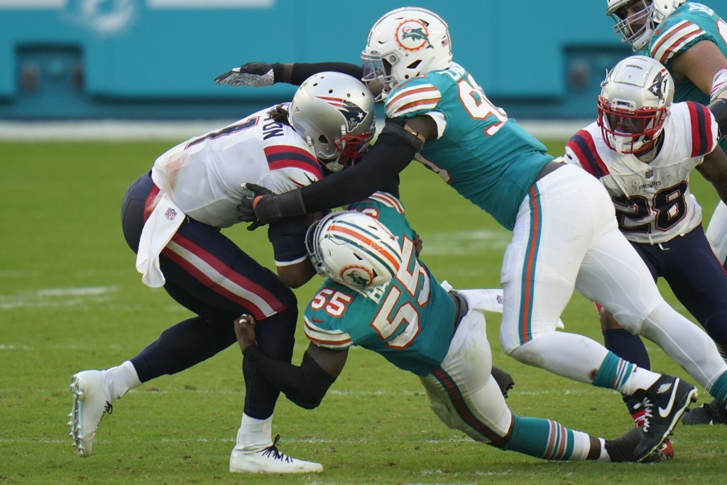 Miami Dolphins outside linebackers Shaq Lawson (90) and Jerome Baker (55) sack New England Patriots quarterback Cam Newton (1) during the second half ...