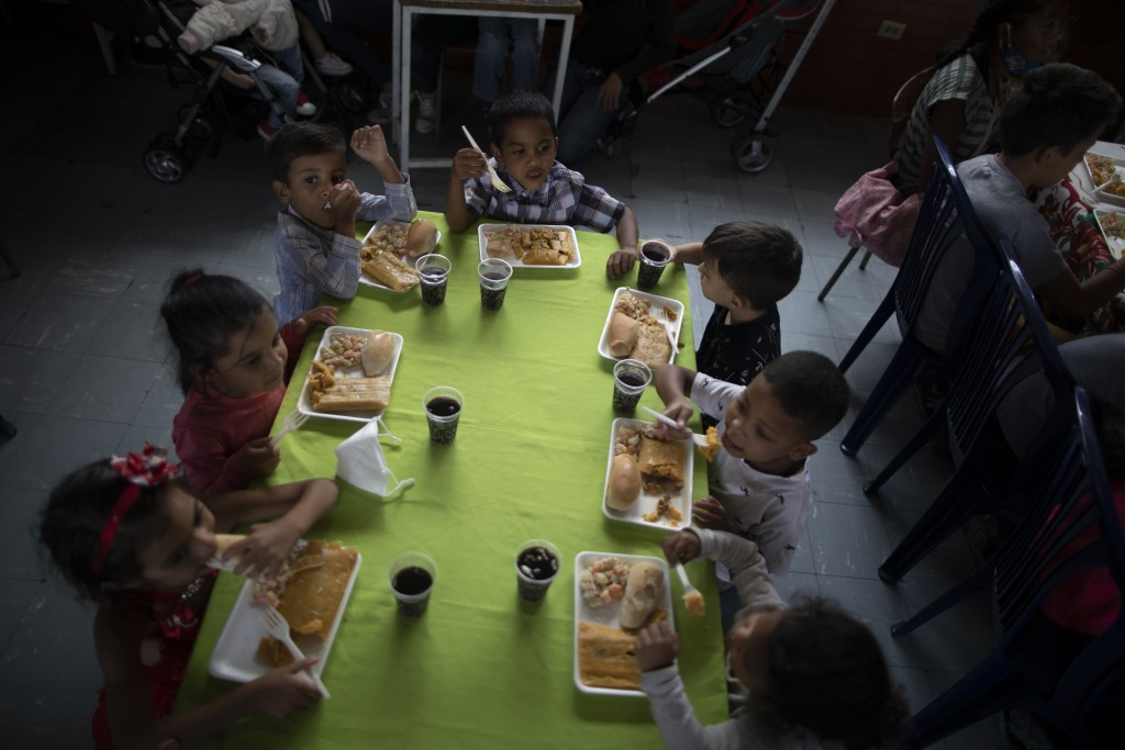 Children eat a free Christmas meal at a soup kitchen in the La Vega area of Caracas, Venezuela, Saturday, Dec.19, 2020. The children dine on a traditi...