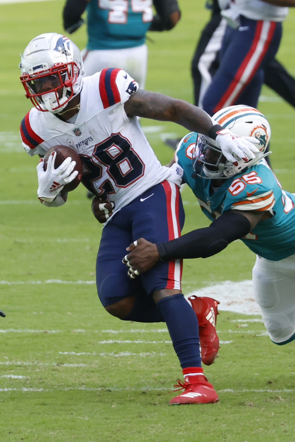 Miami Dolphins outside linebacker Jerome Baker (55) brings down New England Patriots running back James White (28), during the first half of an NFL fo...