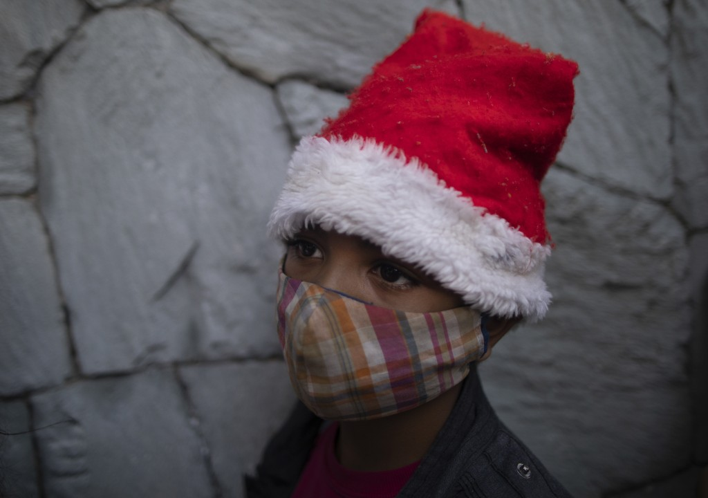 "A boy wearing a Santa Claus hat, and a face mask due to the new coronavirus, waits for a Christmas present donated by volunteers from ""Un Juguete, Una..."