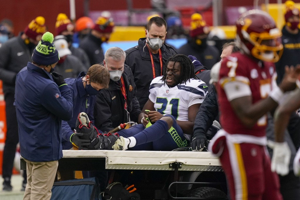 Seattle Seahawks running back DeeJay Dallas (31) reacting to members of the medical team moving him onto a transport cart during the first half of an ...