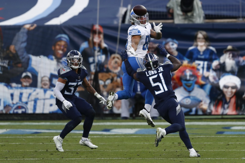 Detroit Lions tight end Hunter Bryant catches a pass over Tennessee Titans linebacker David Long during the second half of an NFL football game Sunday...