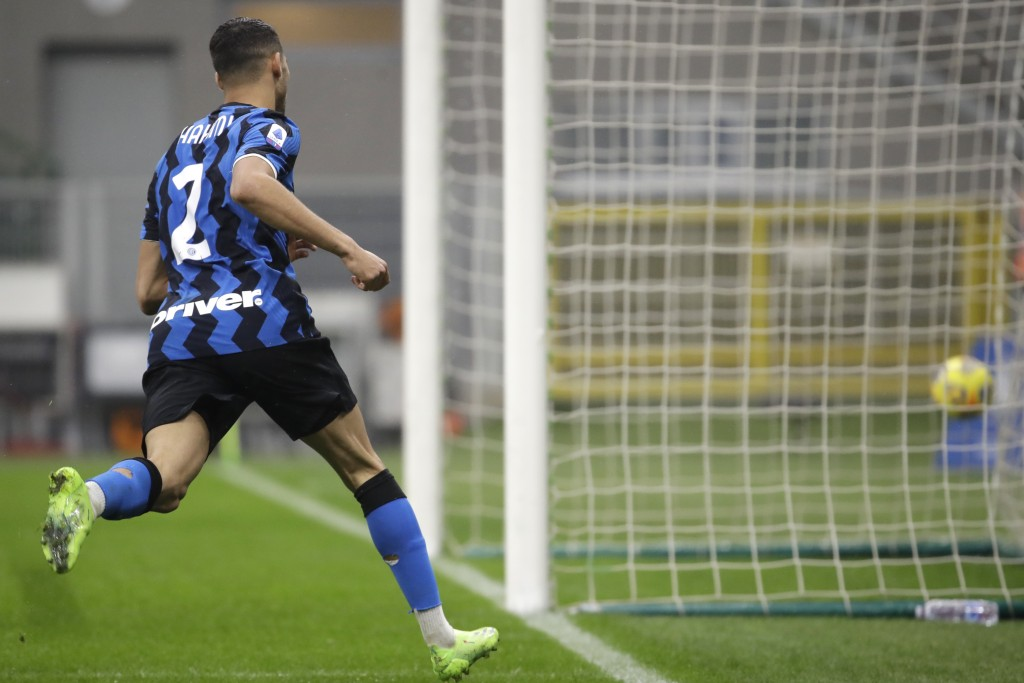 Inter Milan's Achraf Hakimi celebrates after scoring his side's opening goal during the Serie A soccer match between Inter Milan and Spezia, at the Sa...