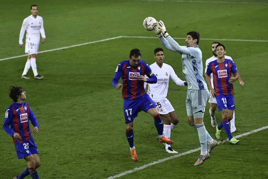 Real Madrid's goalkeeper Thibaut Courtois, controls the ball in front Eibar's Kike Garcia during the Spanish La Liga soccer match between Eibar and Re...