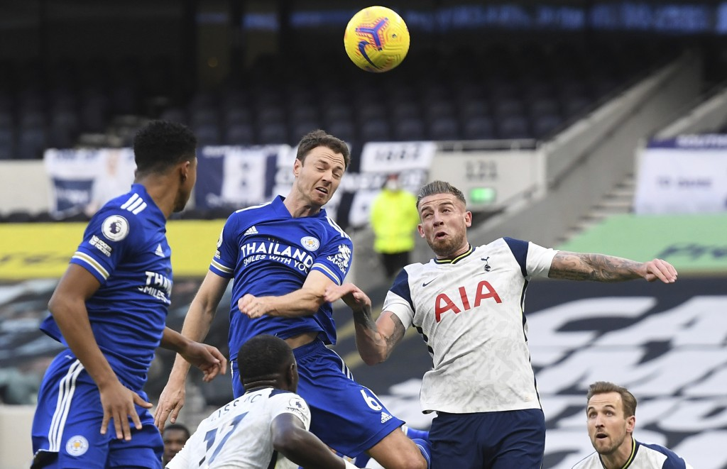 Leicester's Jonny Evans, center, leaps for the ball with Tottenham's Toby Alderweireld, right during the English Premier League soccer match between T...