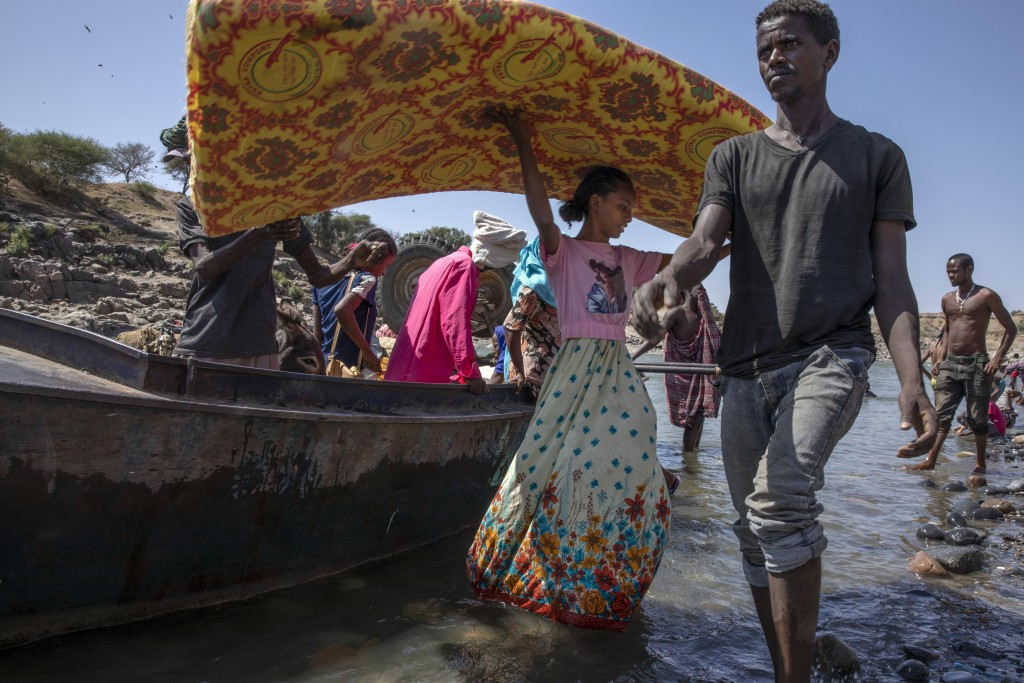 Refugees who fled the conflict in Ethiopia's Tigray region carry their belongings off a boat after arriving on the banks of the Tekeze River on the Su...