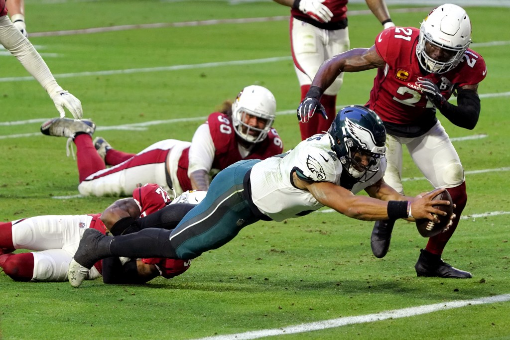 Philadelphia Eagles quarterback Jalen Hurts (2) dives in to the end zone for a touchdown as Arizona Cardinals strong safety Budda Baker and cornerback...
