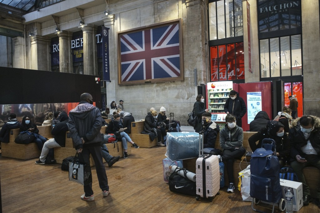 Passengers wearing face mask wait next to the Eurostar Terminal at Gare du Nord train station in Paris, Monday Dec. 21, 2020. France is banning all tr...