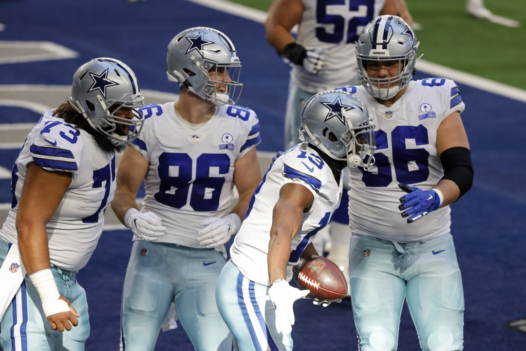 Dallas Cowboys' Joe Looney (73), Dalton Schultz (86), and Connor McGovern (66) celebrate with Michael Gallup (13) after his touchdown catch in the fir...
