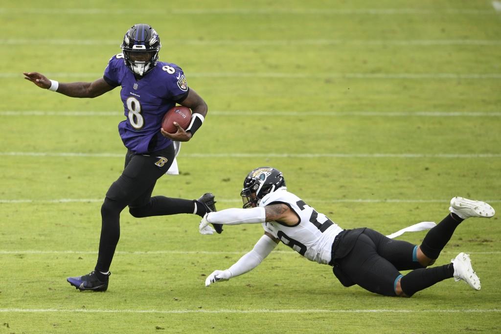 Baltimore Ravens quarterback Lamar Jackson (8) avoids a sack attempt by Jacksonville Jaguars safety Josh Jones (29) during the second half of an NFL f...