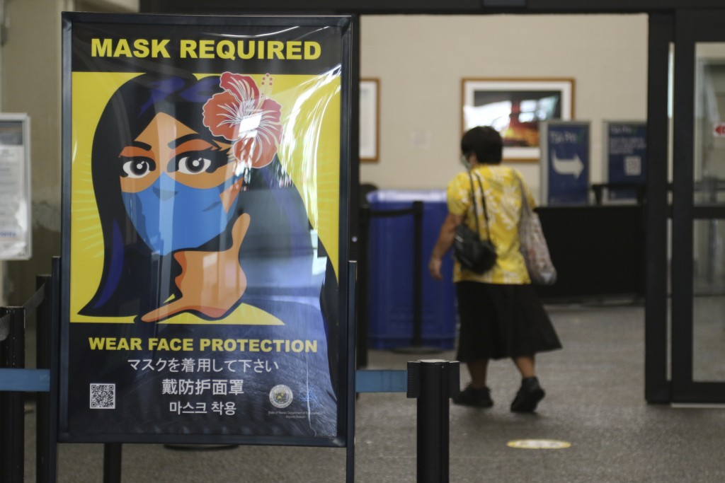 FILE - In this Oct. 2, 2020 file photo, a woman walks into the international airport in Honolulu amid a quarantine rule that effectively shut down the...