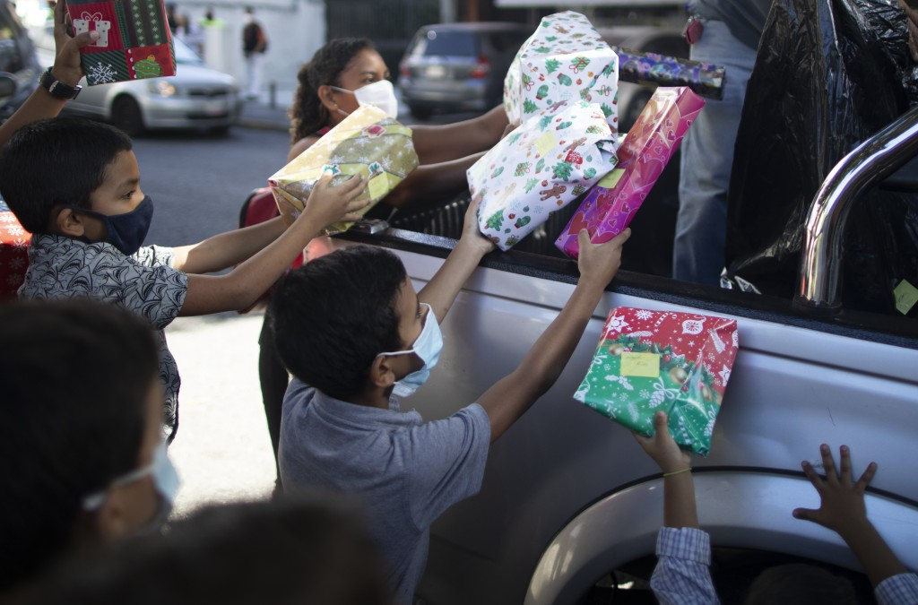 "Children receive Christmas presents donated by the volunteer group ""Un Juguete, Una Buena Noticia,"" or One Toy, One Good News, from the back of a pick..."