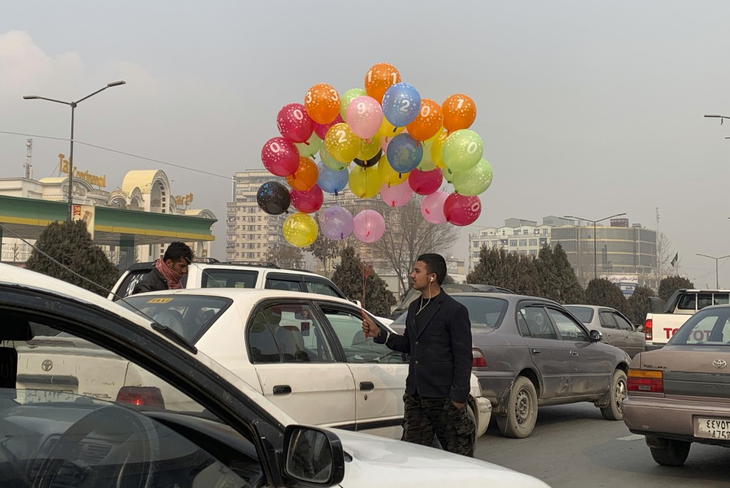 An Afghan balloon vendor looks for customers on a road in Kabul, Afghanistan, Monday, Dec. 21, 2020. (AP Photo/Rahmat Gul)