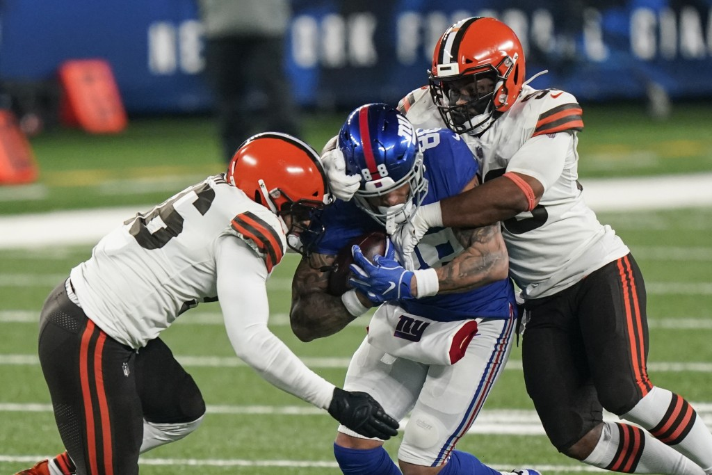 Cleveland Browns' B.J. Goodson, right, and Malcolm Smith, left, tackle New York Giants' Evan Engram, center, during the second half of an NFL football...