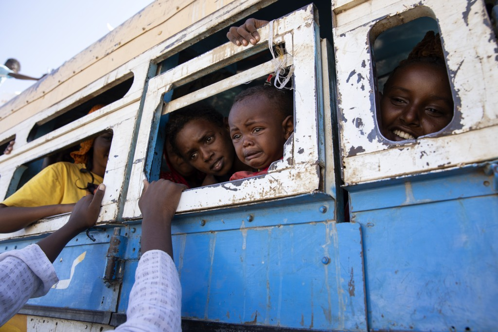 Refugees who fled the conflict in Ethiopia's Tigray region ride a bus going to the Village 8 temporary shelter, near the Sudan-Ethiopia border, in Ham...