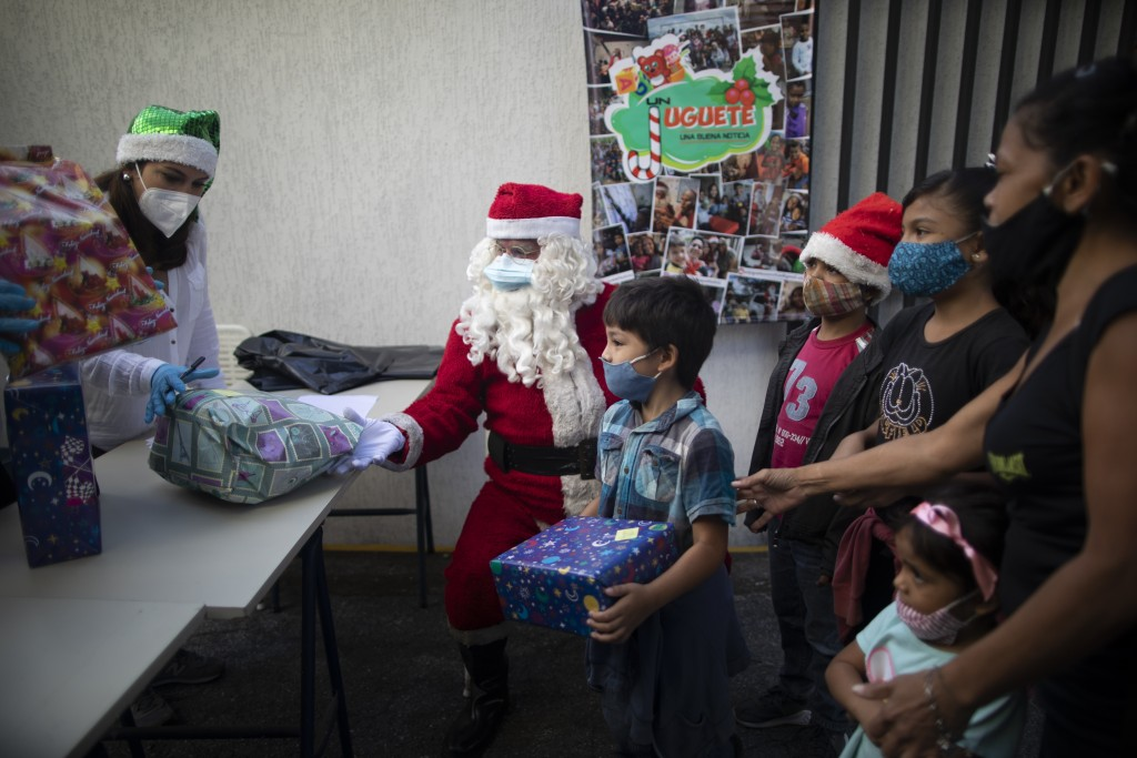 "Children receive Christmas presents donated by the volunteer group ""Un Juguete, Una Buena Noticia,"" or One Toy, One Good News, in Caracas, Venezuela, ..."