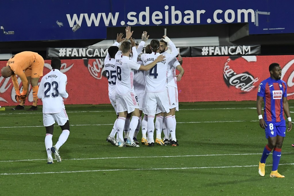 Real Madrid's Luka Modric, center obscured from view, celebrates with teammates after scoring during the Spanish La Liga soccer match between Eibar an...