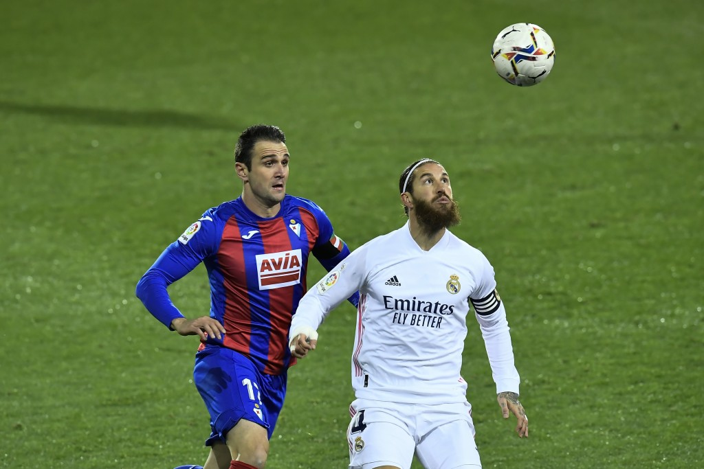 Real Madrid's Sergio Ramos duels for the ball with Eibar's Kike Garcia, right, during the Spanish La Liga soccer match between Eibar and Real Madrid, ...