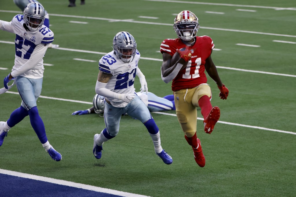 San Francisco 49ers wide receiver Brandon Aiyuk (11) high steps into the end zone after catching a pass for a touchdown in front of Dallas Cowboys' Tr...