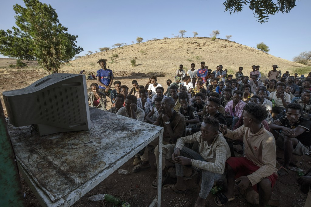 Men who fled the conflict in Ethiopia's Tigray region watch the news on a television, at Umm Rakouba refugee camp in Qadarif, eastern Sudan, Saturday,...