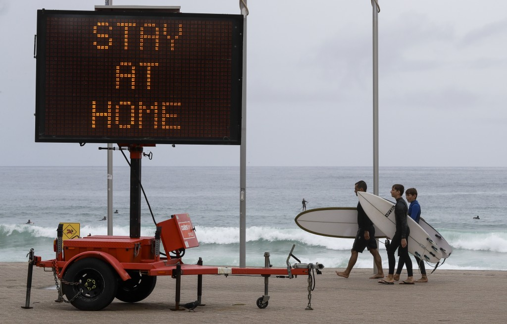 Surfers carry their boards along the beach front at Manly on the northern beaches in Sydney, Australia, Monday, Dec. 21, 2020. Sydney's northern beach...