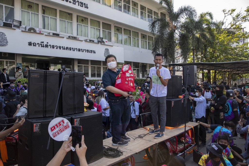 Pro-democracy protest leader Panupong Jadnok, right, speaks as Parit Chiwarak, left, watches from a makeshift stage outside Bang Khen Metropolitan Pol...