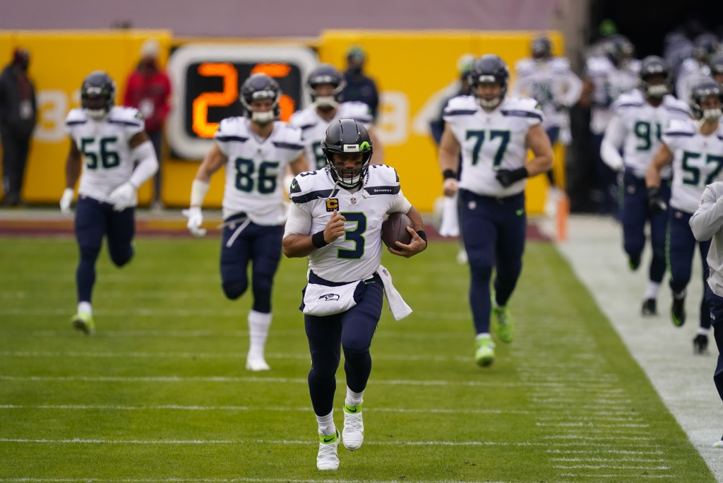 Seattle Seahawks quarterback Russell Wilson (3) runs onto the field before the start of the first half of an NFL football game against the Washington ...