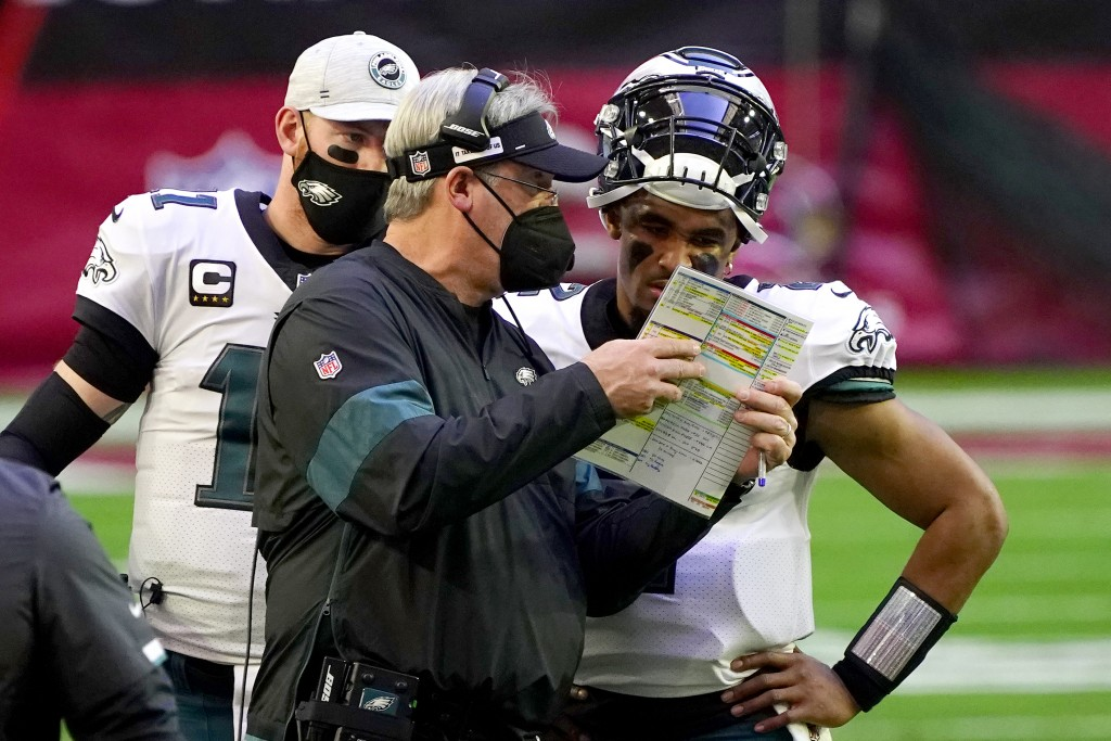 Philadelphia Eagles head coach Doug Pederson talks with starting quarterback Jalen Hurts as quarterback Carson Wentz (11) looks on during the first ha...