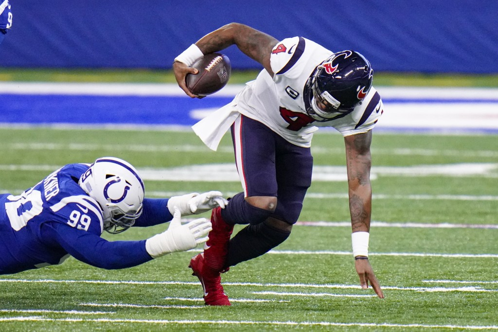 Houston Texans quarterback Deshaun Watson (4) escapes from Indianapolis Colts defensive tackle DeForest Buckner (99) in the first half of an NFL footb...