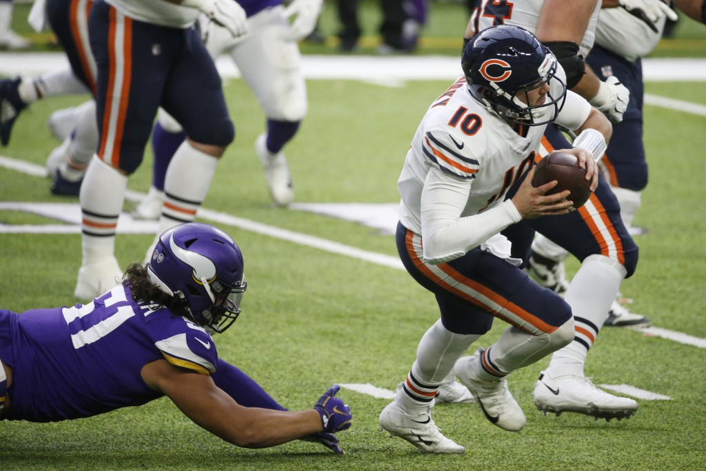 Chicago Bears quarterback Mitchell Trubisky (10) runs from Minnesota Vikings defensive tackle Hercules Mata'afa, left, during the second half of an NF...