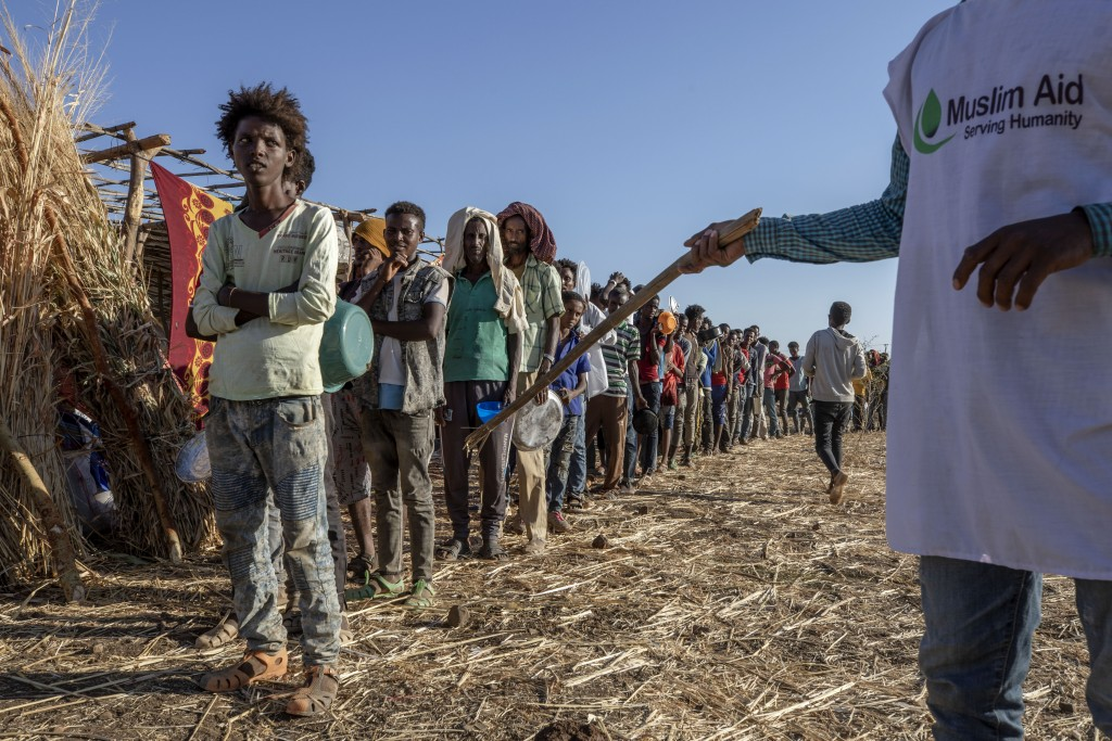A worker for Muslim Aid organizes Tigrayan refugees waiting in line to receive cooked rice and lentils, at Umm Rakouba refugee camp in Qadarif, easter...