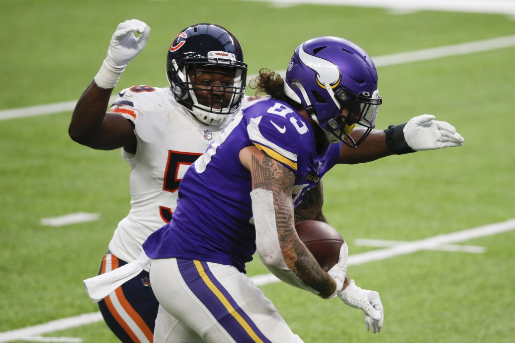 Minnesota Vikings tight end Tyler Conklin (83) runs from Chicago Bears linebacker Roquan Smith, left, during a 20-yard touchdown reception in the seco...