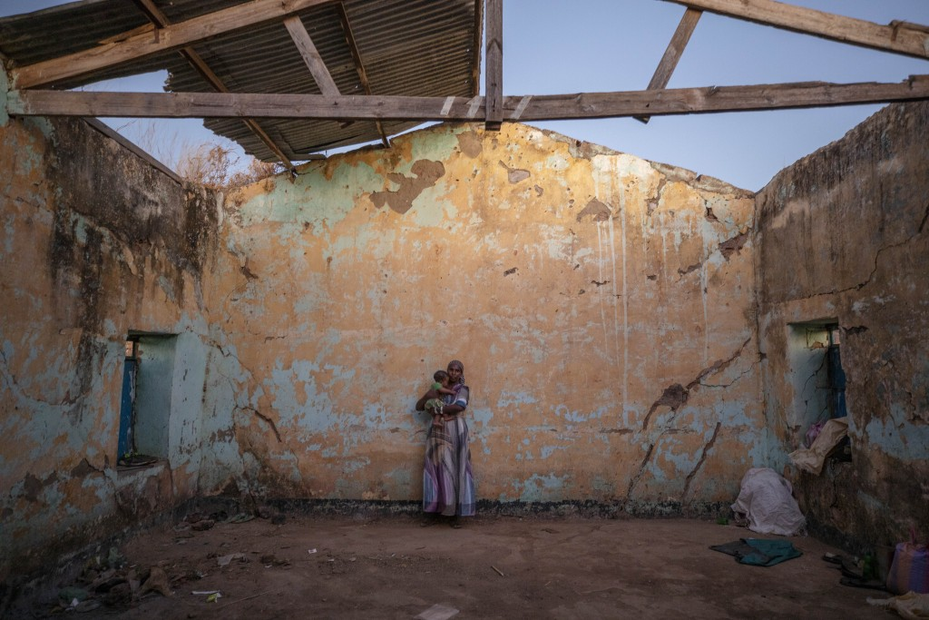 A woman who fled the conflict in Ethiopia's Tigray region holds her child inside of her temporary shelter at Umm Rakouba refugee camp in Qadarif, east...