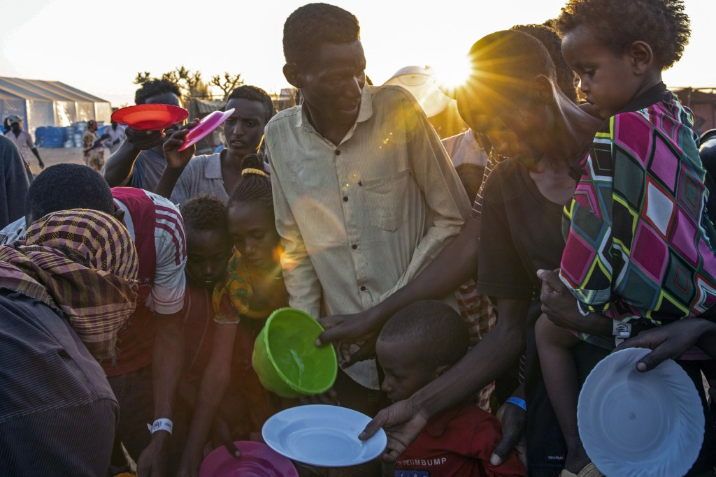 Refugees who fled the conflict in Ethiopia's Tigray region wait to get cooked rice served by Sudanese local volunteers at Um Rakuba refugee camp in Qa...