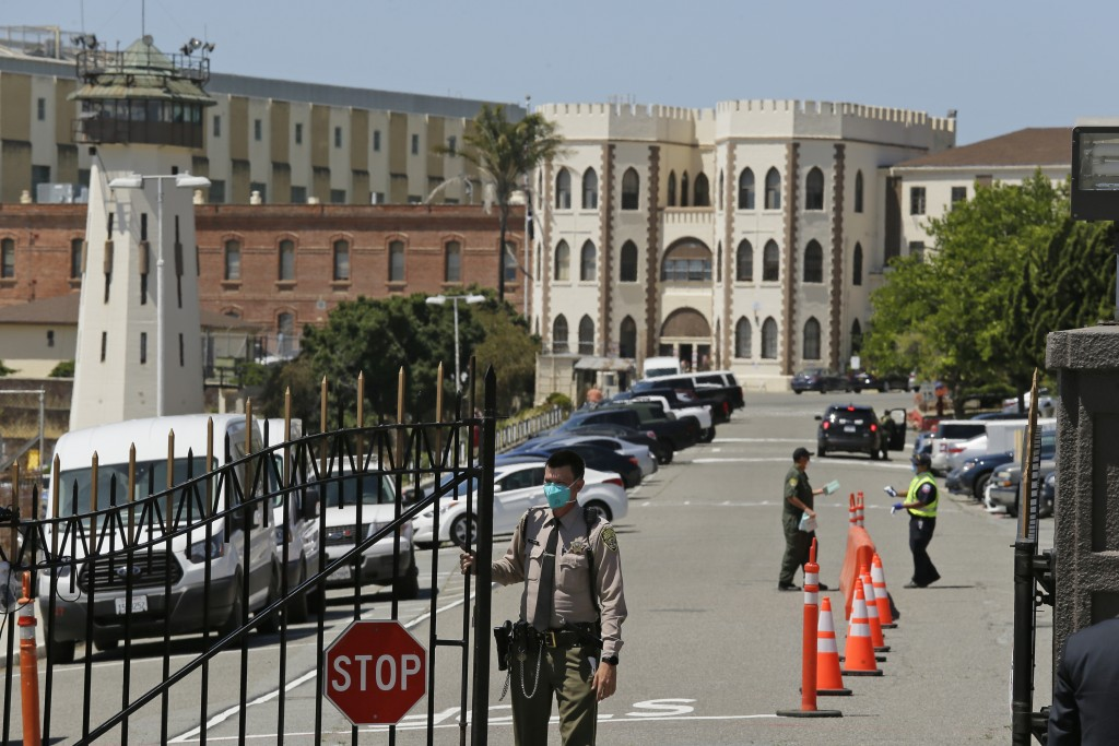 FILE - In this July 9, 2020, file photo, a correctional officer closes the main gate at San Quentin State Prison in San Quentin, Calif. In prisons aro...